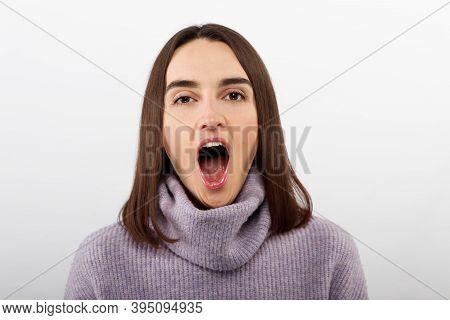 Beautiful Woman Yawns Of Boredom On White Background