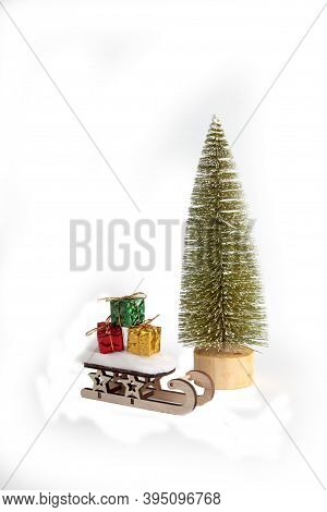 Sledge Loaded With Bright Christmas Gift Isolated On White Background Under A Fir Tree. Winter Holid