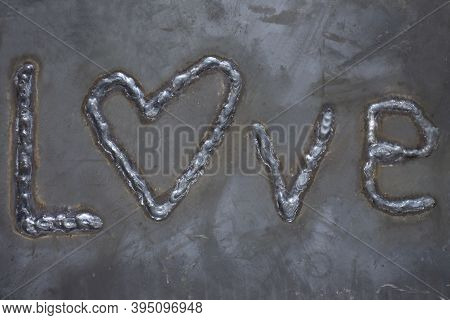 The Inscription Love Is Electric Welding. The Inscription Is Made On A Sheet Of Steel.