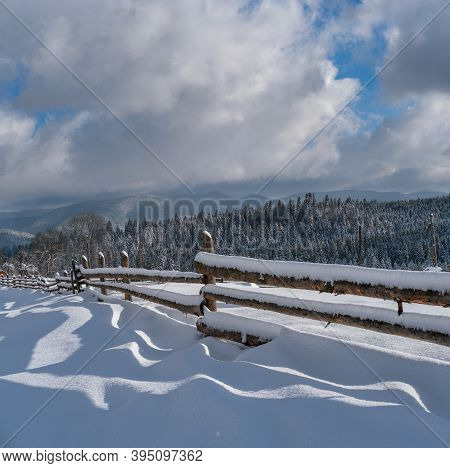 Picturesque Waved Shadows On Snow From Wood Fence. Alpine Mountain Winter Hamlet Outskirts, Snowy Pa