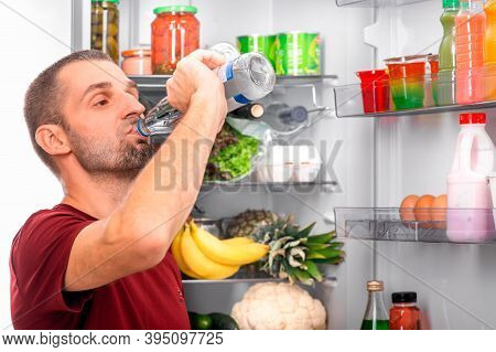A Man Drinks Water From A Glass Bottle Against The Background Of An Open Refrigerator With Food. The