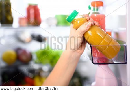 The Girl Takes Out Or Puts On The Shelf A Small Bottle Of Orange Vegetable Or Fruit Juice Against Th