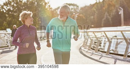 Keep In Shape. Cheerful Active Mature Family Couple In Sportswear Smiling At Each Other While Runnin