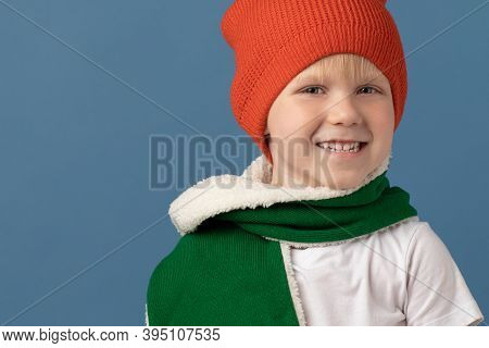 Smiling Boy Of European Appearance, Child In Red Hat And Green Scarf On Blue Background Close-up. St