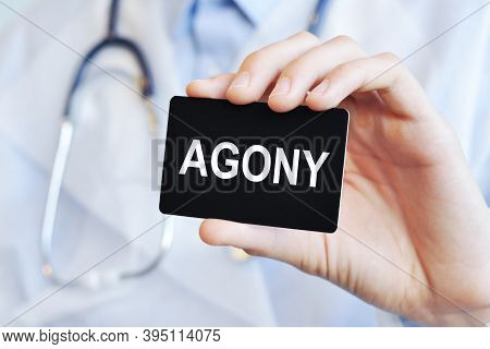 Doctor Holding A Paper Card With Text Agony, Medical Concept