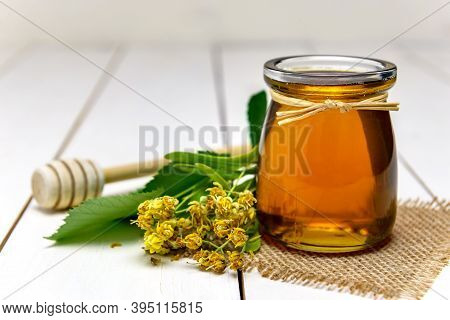 Jar With Linden Honey, Stick For Honey And Fresh Linden Flowers On A Wooden Table.