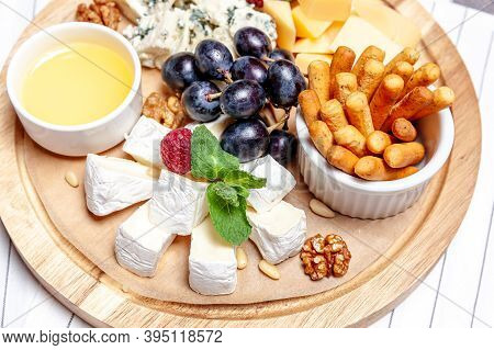 Board With Different Types Of Cheese. Cheeses Mix Set Dor Blu Chedar Parmesan Brie Honey Sauce Finge