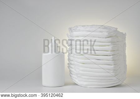 Baby Diapers And Diaper Rash Powder On A White Background. There Is Space For Text.