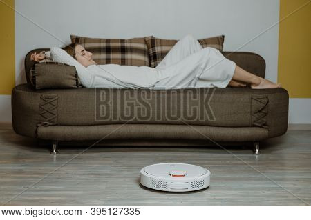 Robotic Vacuums, Robot Mops. Smart Home. Robotic Vacuum Cleaner While Woman Relaxing On Sofa. Automa