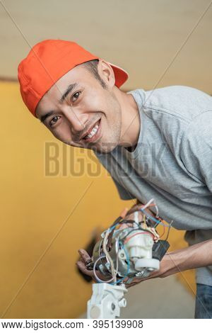 An Electronics Repairman Smiles At The Camera While Opening A Faulty Fan