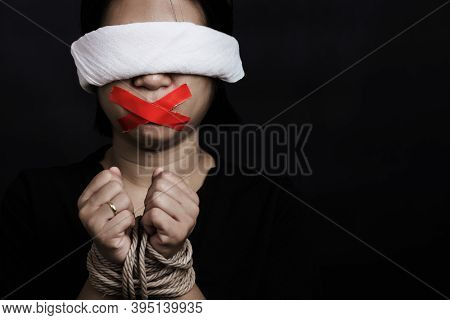Slave Asian Woman Blindfold Wrapping Mouth With Red Adhesive Tape, Tied With Chains And Closed Her E