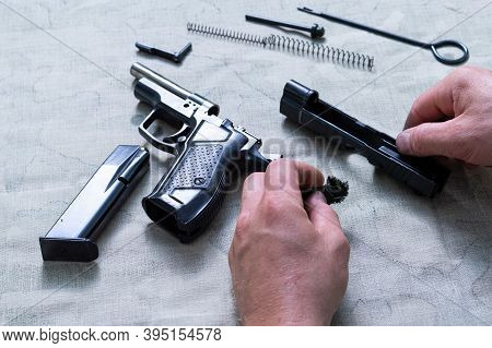 Details Of The Disassembled Pistol. The Hands Of The Master Hold The Frame Of The Pistol.