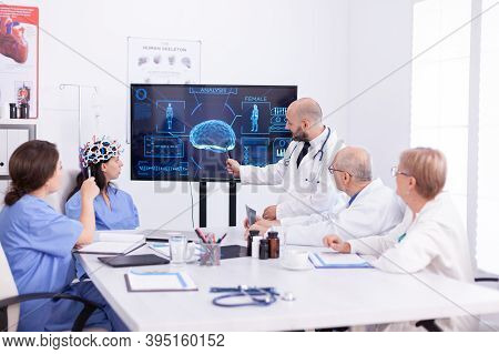 Doctor Talking About Brain Activity During Conference With Medical Staff And Nurse Wearing Headset W