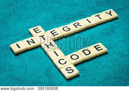 integrity, ethics and code crossword in ivory letters against textured handmade bark paper, moral obligations and conduct concept