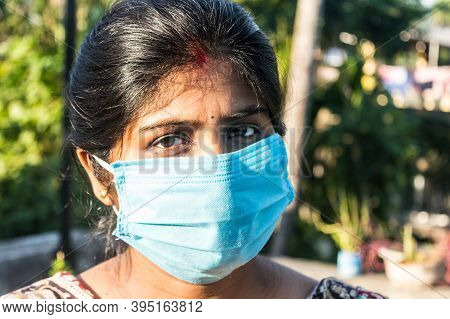 Smiling Face Wearing Mask. Woman Smiling Wearing A Face Mask. Close Up Front View Of A Happy Indian