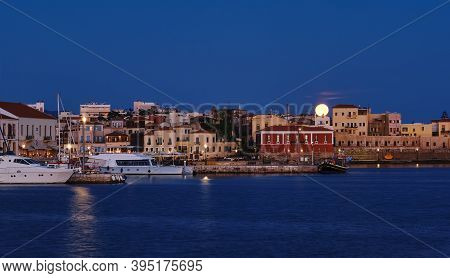Full Moon Setting Over Chanias Old Venetian Harbour. Night View Of Piers, Boats And Maritime Museum