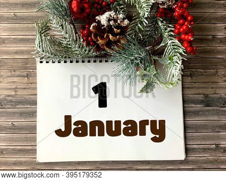 January 1 On A White Notepad.nearby Fir Branches, Red Berries And Cones On A Wooden Background.begin