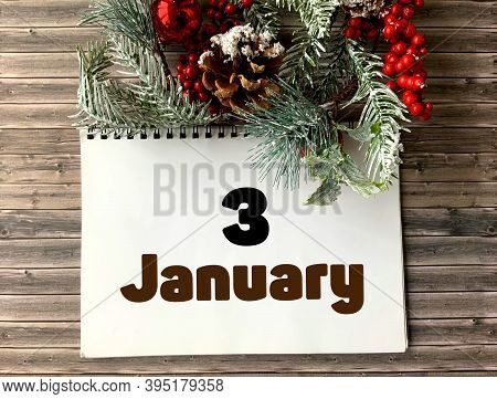 January 3 On A White Notepad.nearby Fir Branches, Red Berries And Cones On A Wooden Background.begin