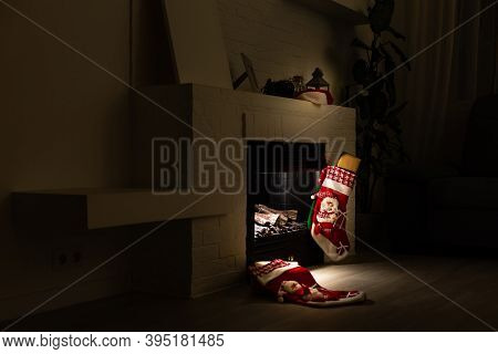 Christmas Stocking Hanging From A Mantel Or Fireplace, Decorated For Christmas With Fire Glowing.