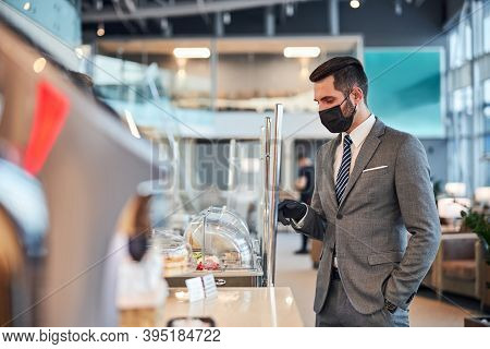 Male In A Medical Mask Choosing Food At A Bistro