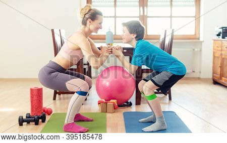 Family doing squats on floor at home during Covid 19 curfew in their home