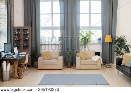 Interior of living-room in modern house or apartment with two armchairs, carpet on the floor, couch, table with computer and cabinet with books