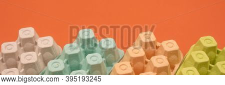 Banner With Multicolored Organic Egg Trays On Orange Background With Copyspace For Your Text. Biodeg