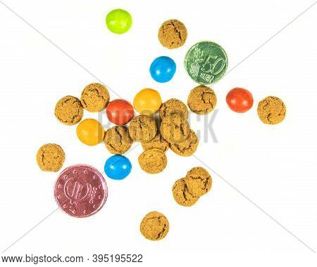 Bunch Of Scattered Pepernoten Cookies And Chocolate Money From Above On White Background For Annual