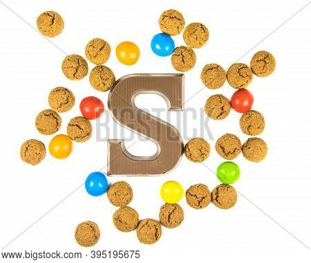 Chocolate Letter S With Bunch Of Scattered Pepernoten Cookies From Above On White Background For Ann
