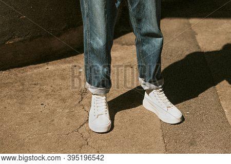 Man in blue jeans white high top sneakers mockup dark tone