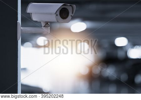 Modern Of Cctv Camera For Monitoring Surveillance And Security On The Wall With Car Park Background.