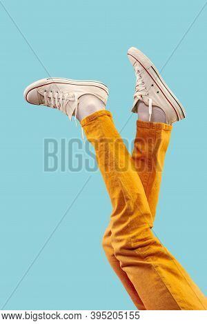 Cropped Shot Of White Footwear, Gumshoes On Blue Studio Background