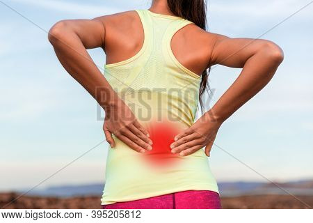 Back pain sport injury woman with inflammed area in red halo. Young athlete touching massaging spine muscles rubbing lower back, cropped torso from behind.