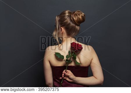 Woman With Blonde Hair Back Head With Updo Hairdo And Red Rose Flower On Black