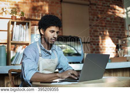 Man Owner Working And Checking Email On Computer. Serious Young African American Guy In Apron Use La