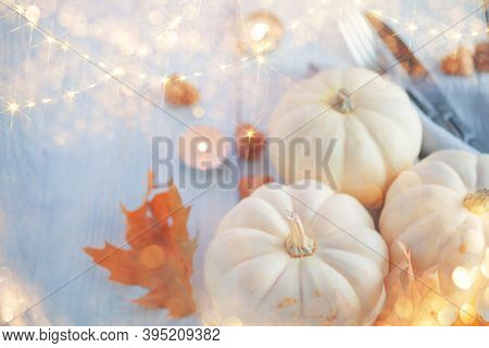 Thanksgiving Day dinner. Holiday served table decorated with pumpkins, autumn bright colorful leaves and burning candles. Beautiful table setting, Thanksgiving backdrop, food background.