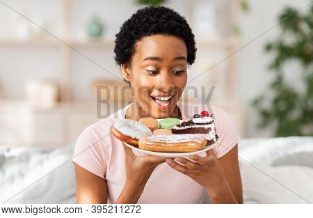 Diet Breakdown And Unhealthy Nutrition Concept. Young African American Lady Holding Plate Of Sweet P