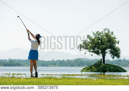 Healthy Sport. Asia Golf Woman Golfer Player Chips And Swing Golf On The Green Floating Water.  Peop