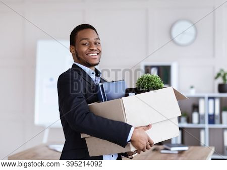 Happy Black Businessman Moving To New Office With Box And His Belongings, Copy Space. Successful Afr