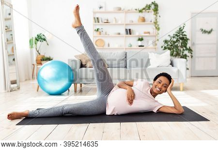 Full Length Portrait Of Expectant Black Woman Exercising On Yoga Mat, Lifting Her Leg Up, Feeling Po