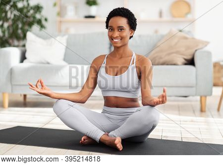 Domestic Sports During Lockdown Concept. Positive Black Woman Meditating In Lotus Pose At Home. Spor