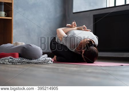 Young Woman Sitting In Child Pose On A Yoga Mat