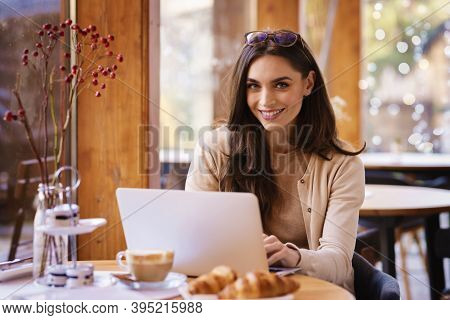 Attractive Woman Using Her Laptop While Sitting At Desk In The Cafe