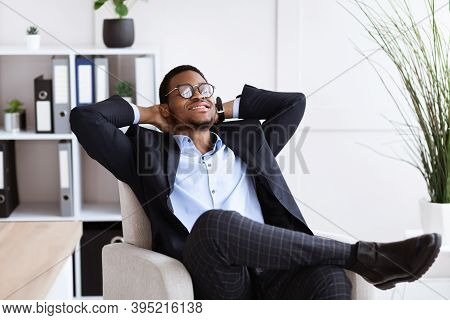 Work Break. Young African American Businessman In Formalwear Relaxing At Workplace, Leaning Back On