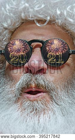 Close-up Shot Of Santa Claus In Stylish Glasses With A Reflection Of 2021 Happy New Year And Salute.