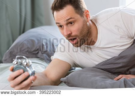 Oversleeping Problem. Shocked Overslept Guy Holding Alarm Clock Lying In Bed, Waking Up Too Late For
