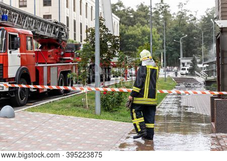 Firemen Un Uniform Standing Behind Fire Tape And Many Fire Engine Trucks With Ladder At Accident In
