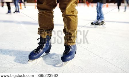 Man Skating On Rink Central Park On Christmas Eve. Legs Of Man Standing On Ice Rink In Skates Close-