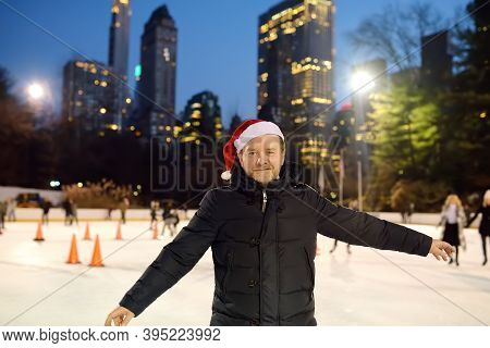 Handsome Man In Santa Claus Hat Skating On Rink Central Park On Christmas Eve. Person Learns To Skat