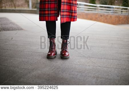 Hipster Wearing Red Trendy Boots And Coat Trench Gray Background